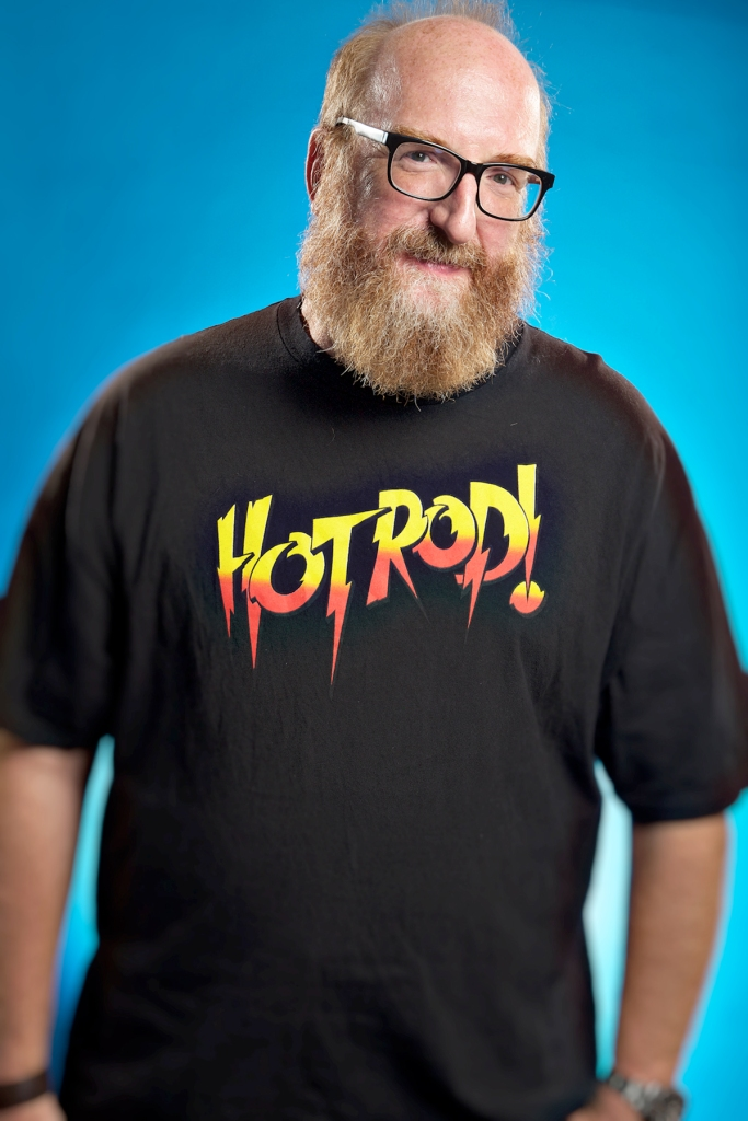 """Brian Posehn in a pattern T-shirt with text """"HOT ROD!"""""""
