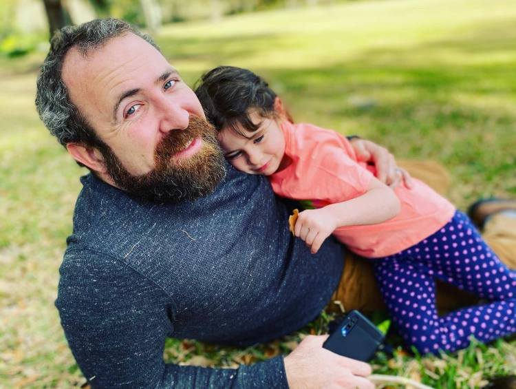 Zach Grant lying on the grass with a child